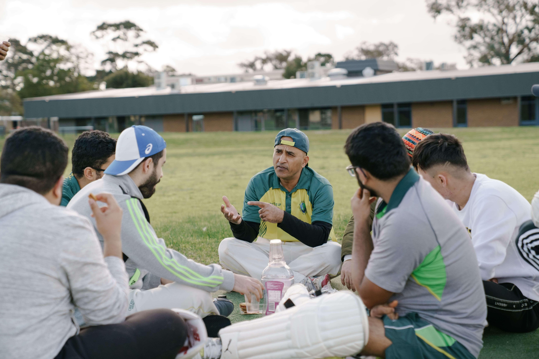 Refugee stories - Abdul sitting talking to cricket team