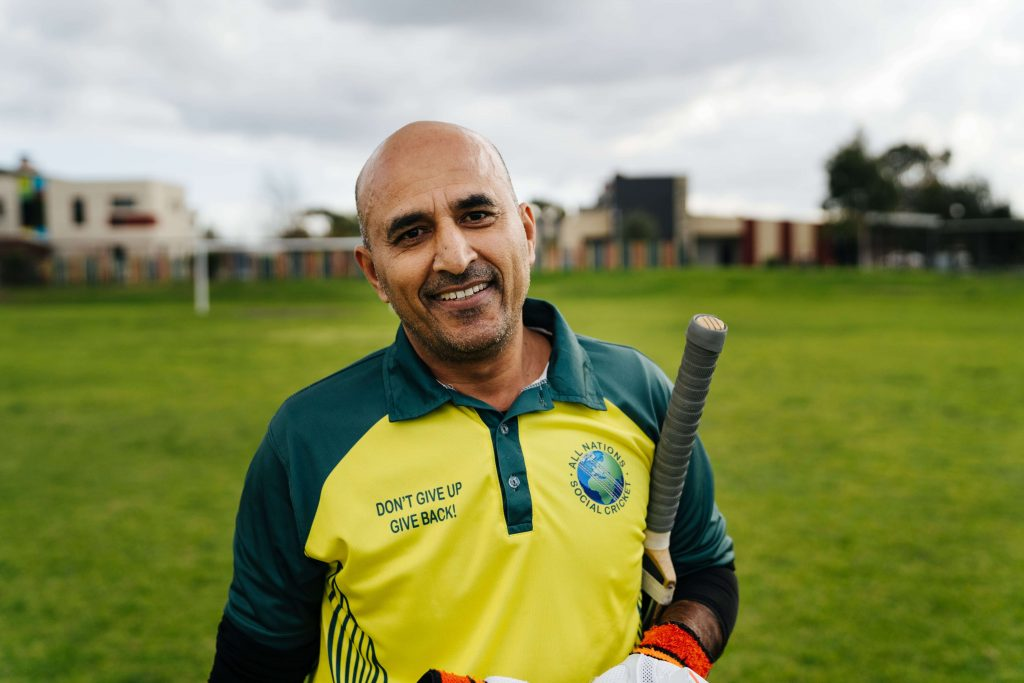 Refugee Stories - Abdul with cricket bat smiling at camera